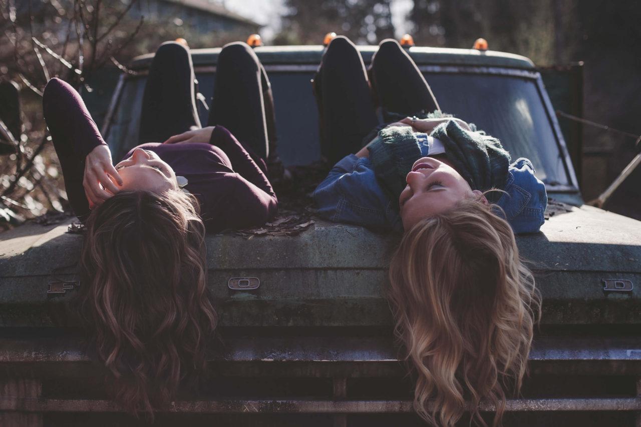 Dos chicas en el capó de un coche