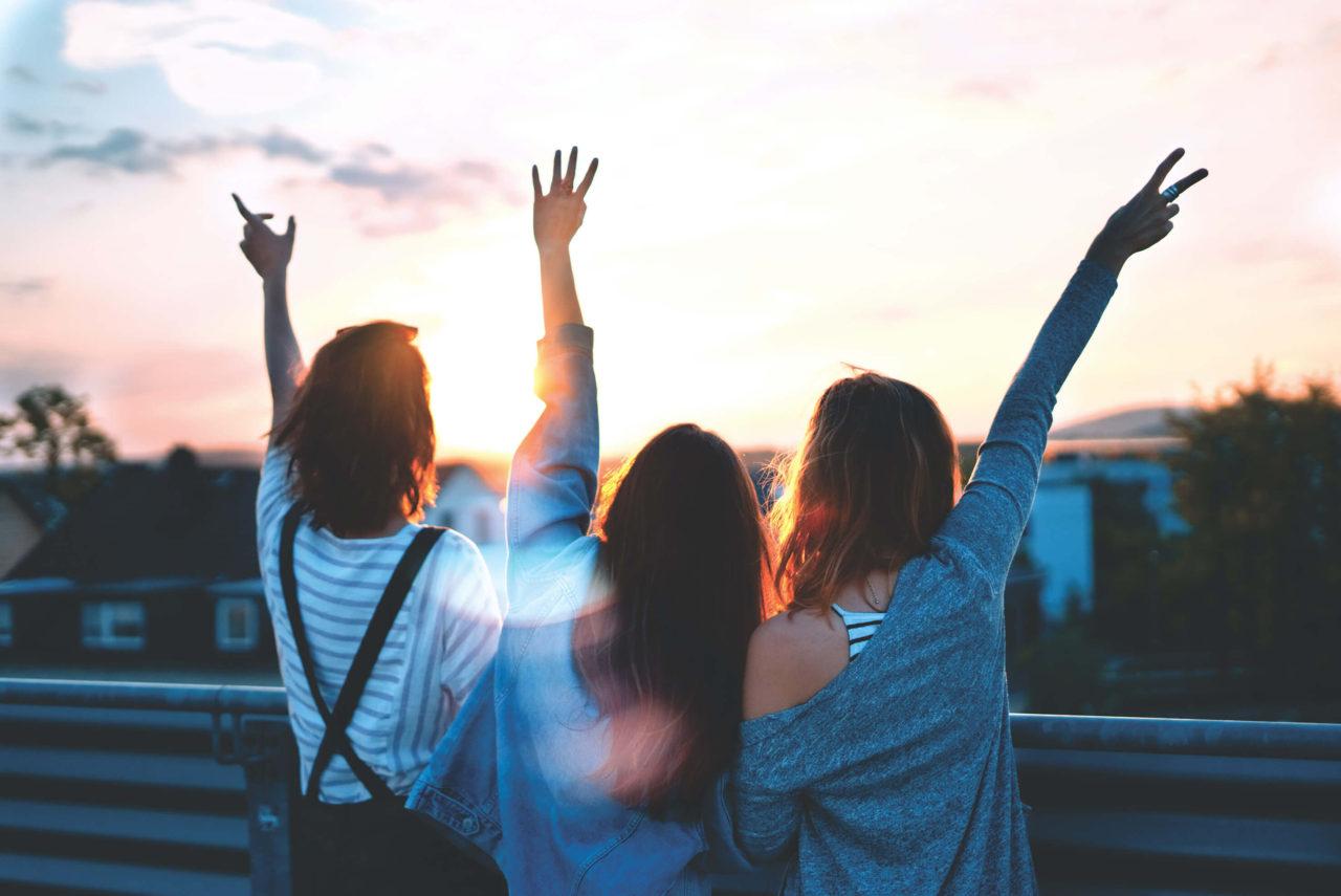 Tres chicas de espaldas saludando